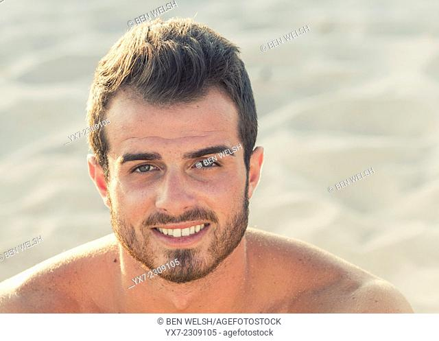 Young man at the beach smiling