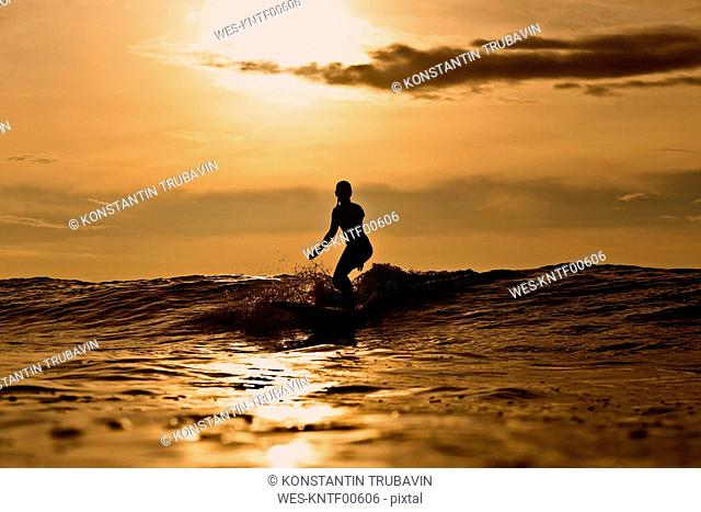Indonesia, Bali, silhouette of woman surfing at sunset