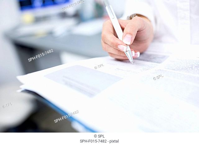 Close-up of dentist's hand writing on file