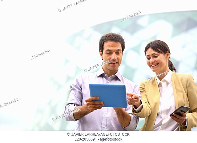 Business man and business woman with tablet and smartphone in business center. San Sebastian Technology Park. Donostia. Gipuzkoa. Basque Country