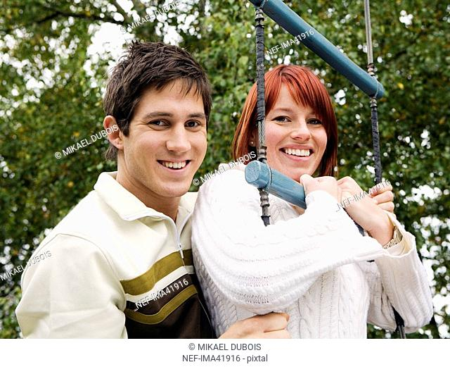 A smiling man and woman in an assault course
