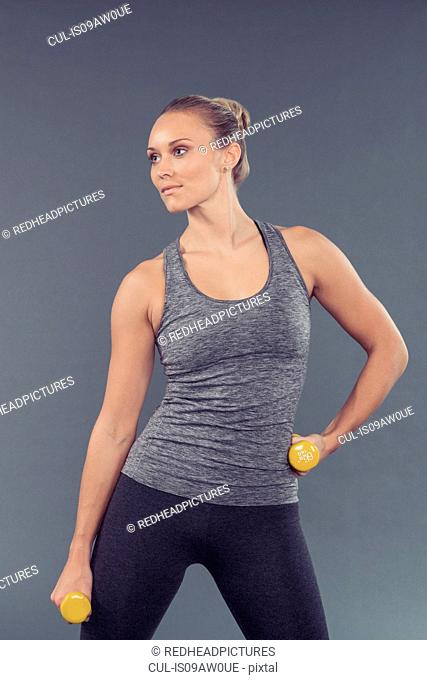 Young woman working out with dumbbells, grey background