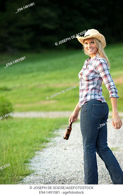Side view of a blond woman wearing blue jeans and a straw hat waliking on a country path looking back at the camera