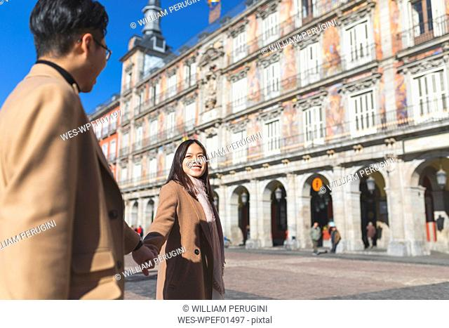 Spain, Madrid, happy young tourist couple holding hands on Plaza Mayor