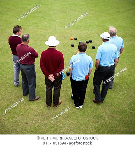 Rear view of 6 men playing lawn bowls , Aberystwyth Wales UK
