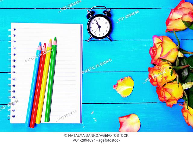 Empty notebook and colorful pencils, top view
