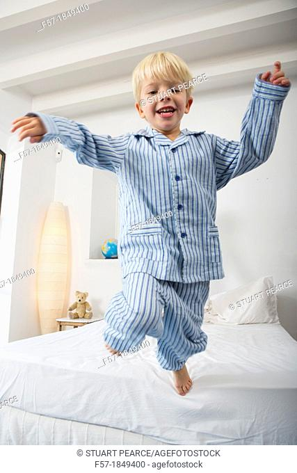 Four year old boy jumping off the bed
