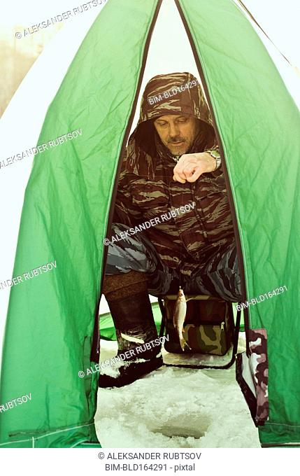 Caucasian hiker ice fishing in tent