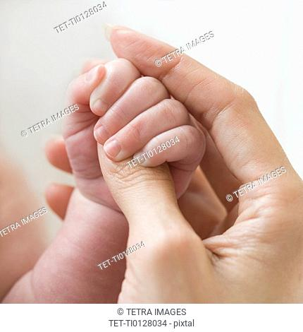 Close up of mother holding baby's hand