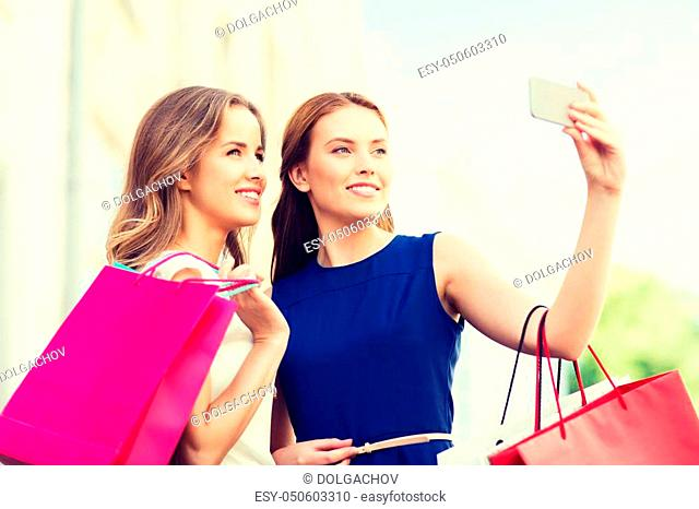 sale, consumerism, technology and people concept - happy young women with shopping bags and smartphone taking selfie on city street