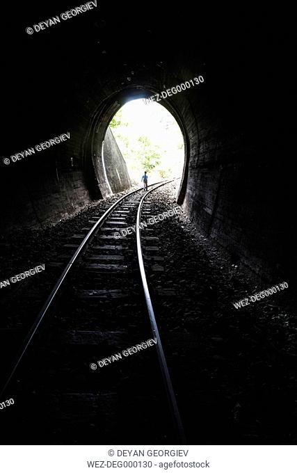 Bulgaria, young boy walking in railroad tunnel