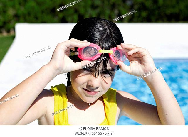 Portrait of little girl wearing swimming goggles at pool