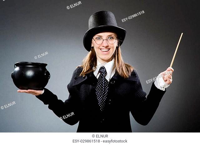 Harry Potter girl with magic stick and pot against gray