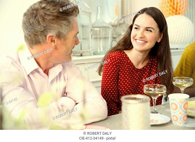 Smiling couple talking and drinking champagne at party table