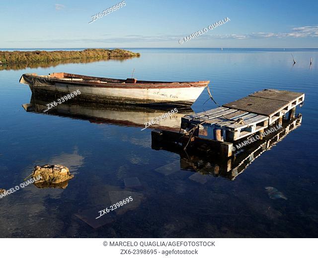 Small fishing boat and handmade palette pier at Alfacs Bay. Ebro River Delta Natural Park, Tarragona province, Catalonia, Spain