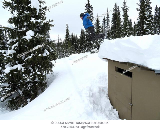 A boy, 13, jumps from a roof into snow in Winter in Jasper National Park, Alberta, Canada