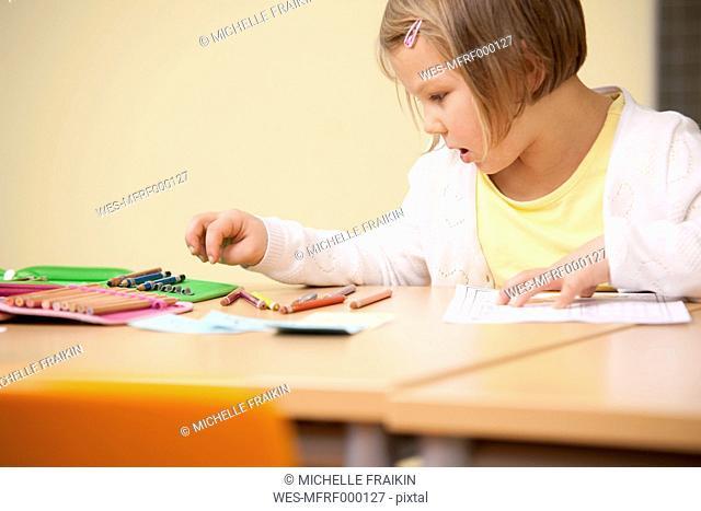 Schoolgirl at school desk with color pencils