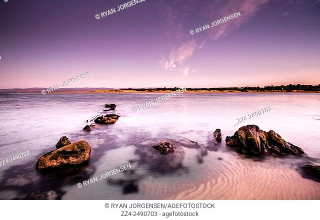 Pre dawn long exposure on a serene sea landscape with hues of purple and violet. Coles Bay, Tasmania, Australia