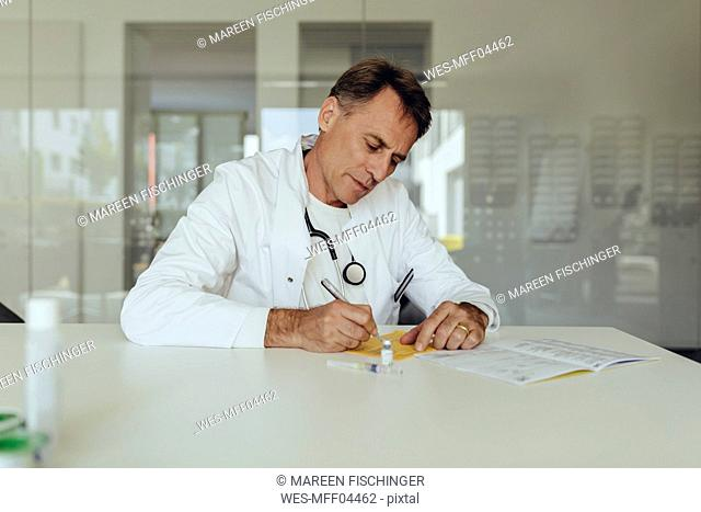 Doctor sitting in practice, filling in immunization card
