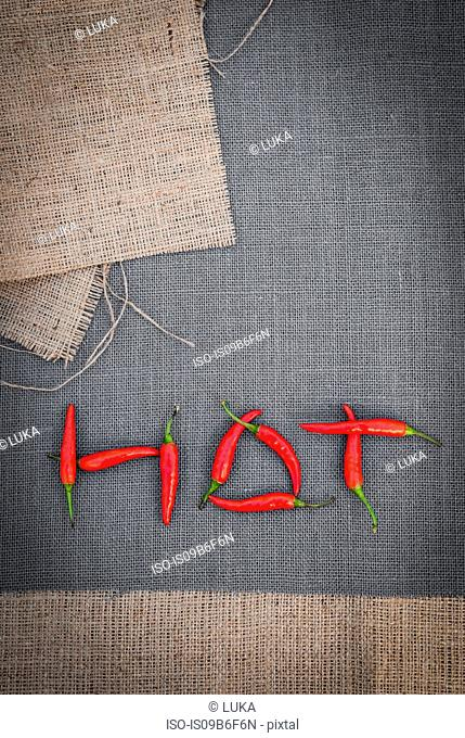 Red chilli peppers arranged to spell the word 'HOT', overhead view