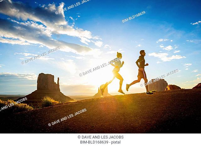 Caucasian couple running in Monument Valley, Utah, United States