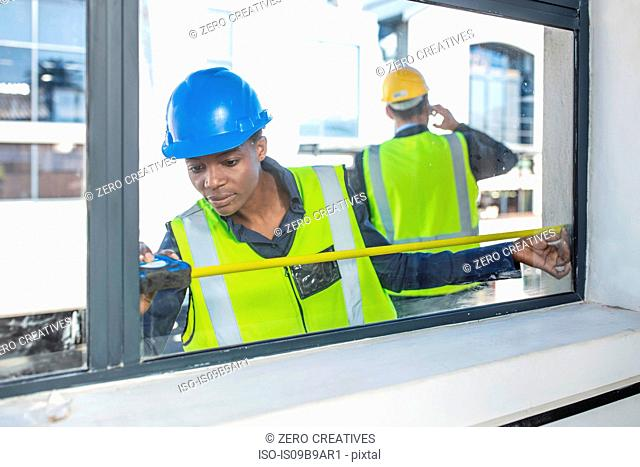 Woman in hard hat and high viz jacket measuring window