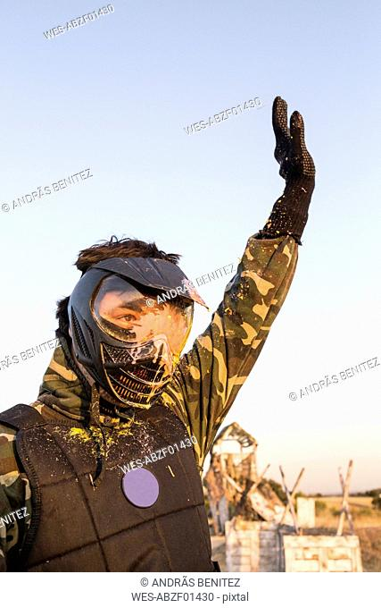 Paintball player with arm raised after being eliminated in a paintball game