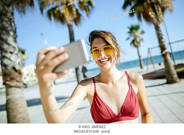 Laughing young woman wearing yellow sunglasses taking a selfie on boardwalk