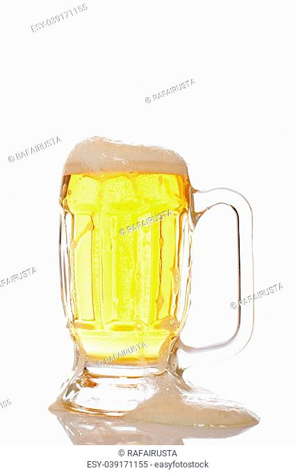 A mug of beer overflowing, reflected on white background