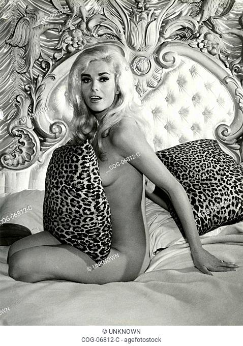 Actress Edy Williams naked covered with leopard-print pillows