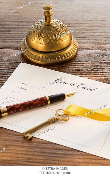 Guest registry card, pen, key and bell on table