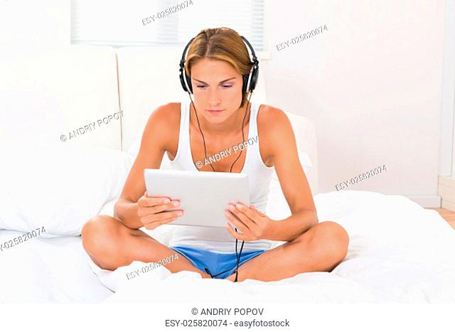 Young Woman Sitting On Bed Using Headphones And Digital Tablet