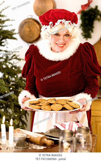 Portrait of Mrs. Claus holding fresh gingerbread cookies