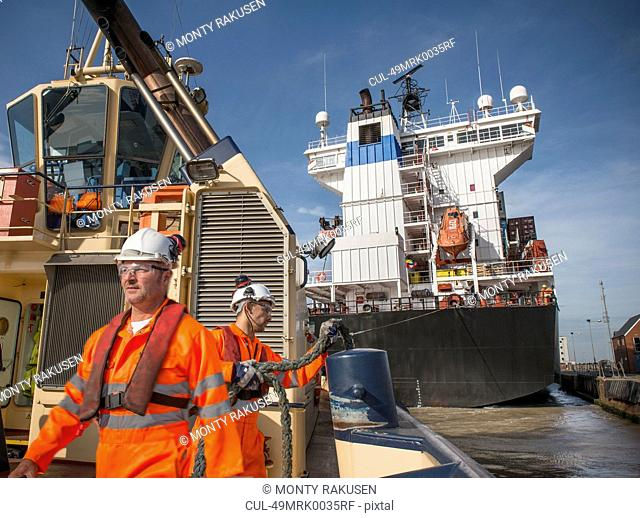 Workers on tug boat pulling in rope