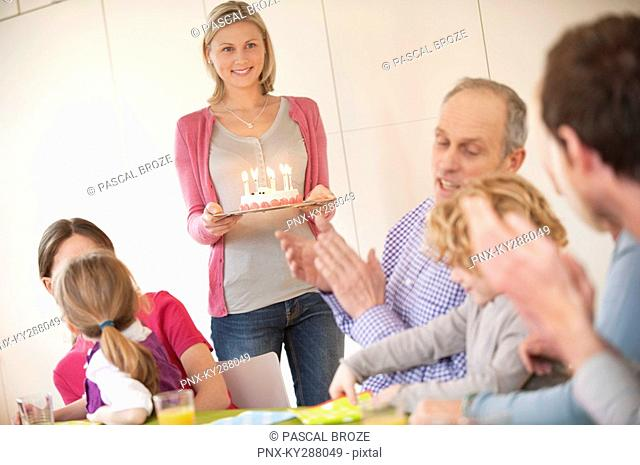 Family at a birthday celebration with a woman bringing cake in the background