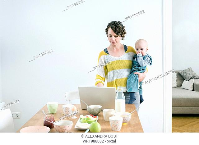 Mother with laptop and children in kitchen