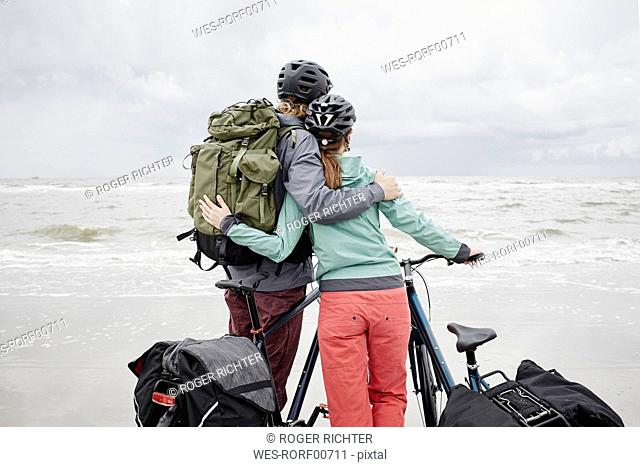 Germany, Schleswig-Holstein, St Peter-Ording, couple with bicycles on the beach