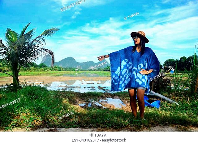 Thai women wear clothes indigo natural color portrait at outdoor near Khao Oktalu Mountain or The Hole Mountain with rice field at Phatthalung province of...