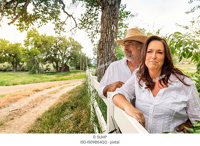 Mature couple leaning against ranch fence, Bridger, Montana, USA
