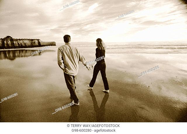 Couple enjoying a soulful sunset stroll in black and white