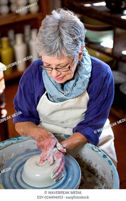 Attentive female potter making pot
