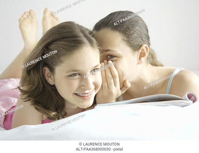Preteen girl whispering to friend