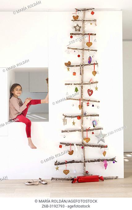 Little girl seated by a Christmas tree