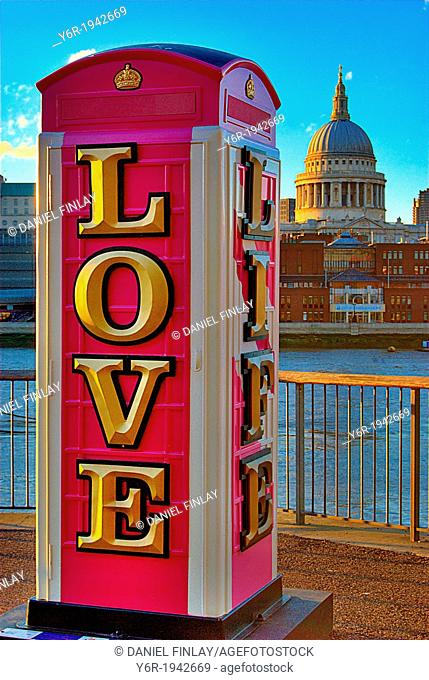 "Modern art installation telephone box bearing the message """"love life"""" , on the banks of the River Thames in London, England, with St"