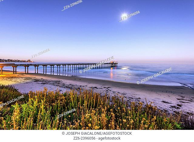 Early morning view of the ocean and the Ellen Browning Scripps Pier with the Moon overhead. San Diego, California, United States