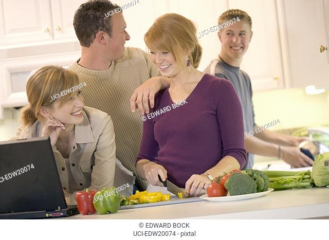 Woman using laptop with friends cooking in kitchen