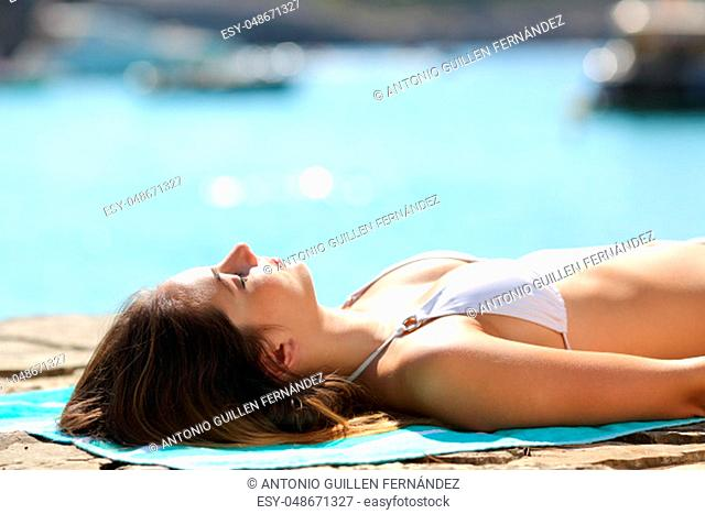 Relaxed woman sunbathing on the beach on summer vacation