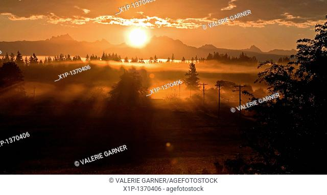 This stunning sunrise is coming over the mountain known as 3 Sisters or 3 Fingers called both commonly in Washington state  A heavy fog is laced in and...