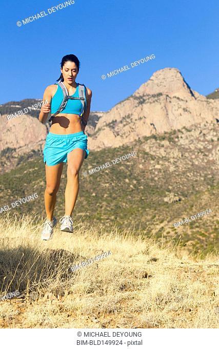 Hispanic woman running in remote area