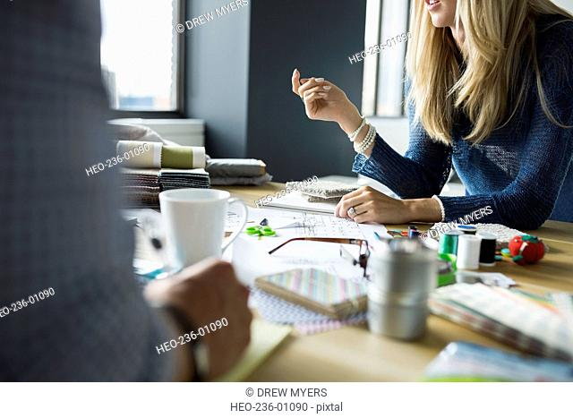 Architect and interior designer reviewing swatches and blueprints